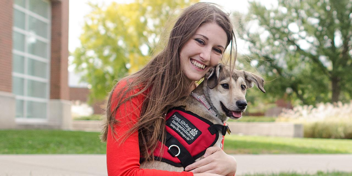 Student hugging a dog.