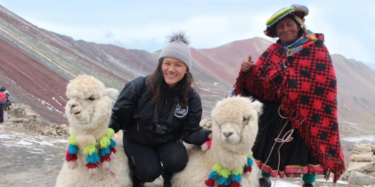 Study abroad student in mountains with al pacas